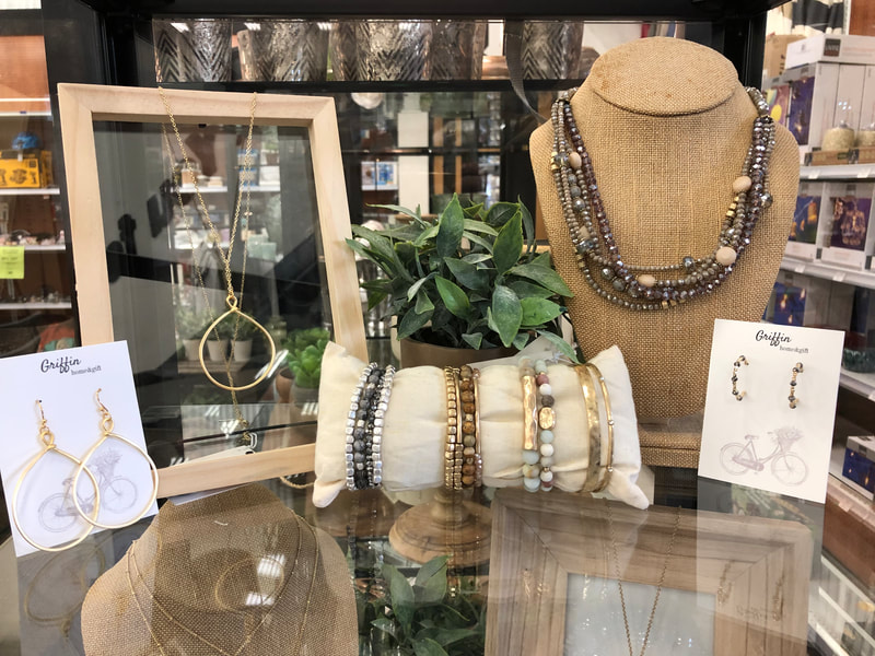 Jewelry selection including earrings, necklaces and bracelets displayed on glass table